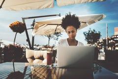 有膝上型计算机的蓬松卷发卷曲女孩在街道咖啡馆 免版税库存图片