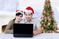 有膝上型计算机的西班牙人享受圣诞节 免版税库存图片