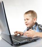 有膝上型计算机的计算机瘾情感男孩 免版税库存图片