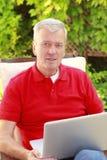 有膝上型计算机的退休的人 图库摄影