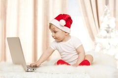 有膝上型计算机的逗人喜爱的圣诞老人婴孩 图库摄影