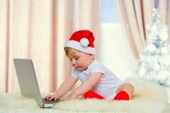 有膝上型计算机的逗人喜爱的圣诞老人婴孩 免版税库存图片