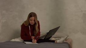 有膝上型计算机的逗人喜爱的女学生学习在卧室的 股票录像