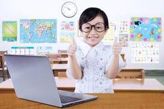 有膝上型计算机的逗人喜爱的女孩在类显示赞许 免版税库存照片