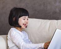 有膝上型计算机的逗人喜爱的女孩 免版税库存照片
