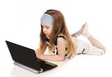 有膝上型计算机的逗人喜爱的小女孩  免版税图库摄影