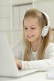 有膝上型计算机的逗人喜爱的小女孩 免版税库存图片
