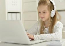 有膝上型计算机的逗人喜爱的小女孩 图库摄影