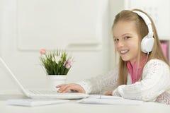 有膝上型计算机的逗人喜爱的小女孩 库存图片