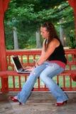 有膝上型计算机的青少年的女孩在长凳 免版税库存图片