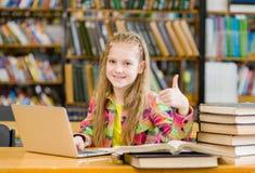有膝上型计算机的青少年的女孩在显示赞许的图书馆里 免版税库存图片