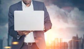 有膝上型计算机的非裔美国人的人在一个被弄脏的城市 免版税图库摄影