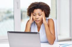 有膝上型计算机的非洲妇女在办公室 库存图片