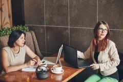 有膝上型计算机的,笔记本两名年轻白种人女实业家 咖啡馆的妇女 免版税库存照片