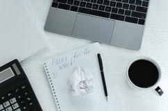 有膝上型计算机的,计算器,咖啡营业所工作场所 一个工作计划一个星期在笔记薄被草拟 免版税库存图片