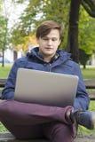 有膝上型计算机的年轻人在公园 免版税库存照片
