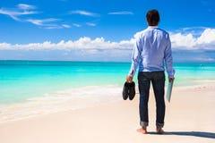 有膝上型计算机的年轻人在绿松石海洋背景热带海滩的 库存图片