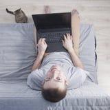 有膝上型计算机的年轻人坐长沙发和猫 顶视图 免版税库存照片