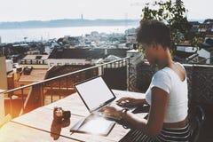 有膝上型计算机的黑人学生女孩在阳台 库存图片
