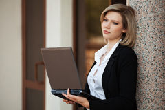有膝上型计算机的年轻女商人在办公楼 免版税库存图片