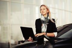 有膝上型计算机的年轻女商人在汽车停车处 免版税库存照片