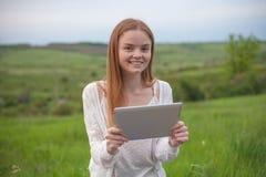 有膝上型计算机的年轻微笑的妇女在看对照相机的公园 库存照片