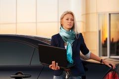 有膝上型计算机的年轻时装业妇女乘她的汽车 库存图片