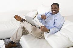 有膝上型计算机的轻松的人坐沙发 免版税库存照片