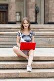 有膝上型计算机的年轻美丽的妇女坐台阶在大学附近 库存图片