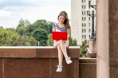 有膝上型计算机的年轻美丽的妇女坐台阶在大学附近 图库摄影