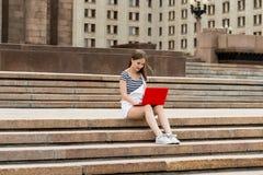 有膝上型计算机的年轻美丽的妇女坐台阶在大学附近 免版税库存照片