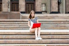有膝上型计算机的年轻美丽的妇女坐台阶在大学附近 免版税图库摄影