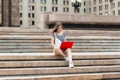 有膝上型计算机的年轻美丽的妇女坐台阶在大学附近 库存照片