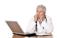 有膝上型计算机的年长医生 免版税库存照片
