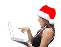 有膝上型计算机笔记本的圣诞节妇女在圣诞老人帽子 免版税图库摄影