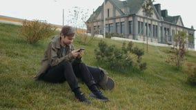 有膝上型计算机袋子的可爱的年轻人走沿城市河和拜访有电话的电话坐草  股票录像