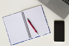 有膝上型计算机键盘、开放五颜六色的笔记本、红色笔和手机的白色书桌 平的位置,顶视图 库存照片