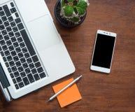 有膝上型计算机键盘的空白的黑屏幕和零件的智能手机在木书桌上的 库存图片