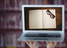 有膝上型计算机陈列的手打开书和玻璃反对有紫色覆盖物的模糊的书架 免版税库存图片