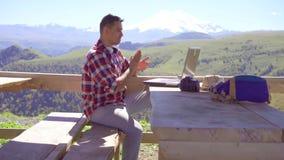 有膝上型计算机高兴的成功的人自由职业者,与山在背景中 影视素材