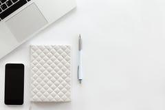 有膝上型计算机,手机,笔的零件的白色办公桌 免版税库存照片