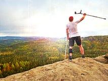 有膝盖关节稳定绷带和前臂杆的远足者 峭壁的远足者做胜利姿态 多小山横向 库存图片