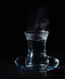有膨胀的透明玻璃杯子开水到它里 从上面的蒸气 黑色背景 库存图片