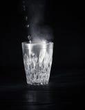 有膨胀的透明玻璃杯子开水到它里 从上面的蒸气 黑色背景 免版税库存照片