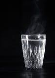 有膨胀的透明玻璃杯子开水到它里 从上面的蒸气 黑色背景 免版税库存图片