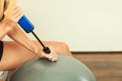 有膨胀适合的球的气泵的健身妇女 免版税库存图片