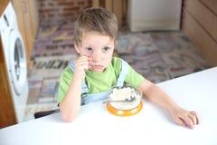 有膳食的男孩在桌上 图库摄影