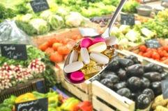 有膳食补充剂的匙子在被弄脏的果子背景 图库摄影