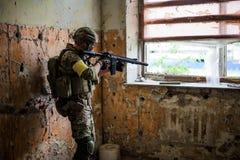 有自动步枪的狙击手由在大厦的窗口 免版税图库摄影