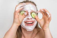有自然奶油色面具的在她的面孔的妇女和黄瓜 库存图片